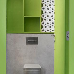 Imagen de aseo industrial con sanitario de pared, paredes verdes y suelo gris