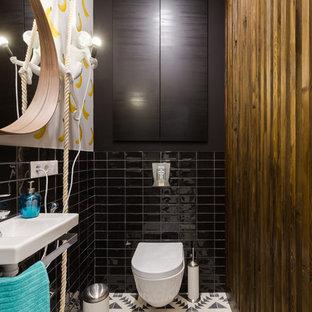 Создайте стильный интерьер: маленький туалет в современном стиле с инсталляцией, черной плиткой, белыми стенами, полом из цементной плитки, разноцветным полом, керамической плиткой и подвесной раковиной - последний тренд