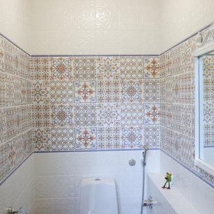 他の地域の小さいカントリー風おしゃれなトイレ・洗面所 (一体型トイレ、白いタイル、セラミックタイル、マルチカラーの壁、セラミックタイルの床、茶色い床、塗装板張りの天井) の写真