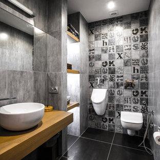 Ejemplo de aseo contemporáneo con urinario, baldosas y/o azulejos grises, lavabo sobreencimera, encimera de madera y suelo negro