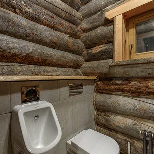 Inredning av ett rustikt toalett, med ett fristående handfat, ett urinoar, grå väggar och grått golv