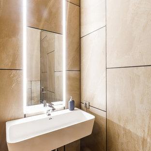Пример оригинального дизайна: туалет в современном стиле с бежевой плиткой, коричневой плиткой, подвесной раковиной и коричневым полом