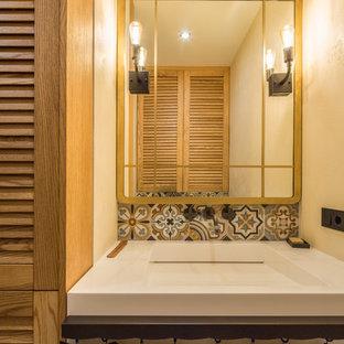 На фото: маленькие туалеты в современном стиле с фасадами с филенкой типа жалюзи, светлыми деревянными фасадами, инсталляцией, бежевыми стенами, полом из керамической плитки, раковиной с пьедесталом, столешницей из искусственного камня, бежевым полом и бежевой столешницей