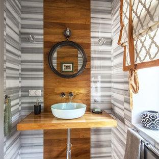 Idées déco pour un WC et toilettes contemporain de taille moyenne avec un placard sans porte, des portes de placard en bois brun, un WC suspendu, un carrelage gris, du carrelage en marbre, un mur gris, un sol en bois brun, un plan vasque, un plan de toilette en bois, un sol jaune et un plan de toilette jaune.