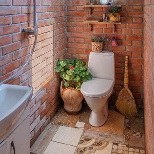 На фото: туалет среднего размера в стиле кантри с унитазом-моноблоком, оранжевой плиткой, серыми стенами, полом из керамической плитки, накладной раковиной и разноцветным полом с