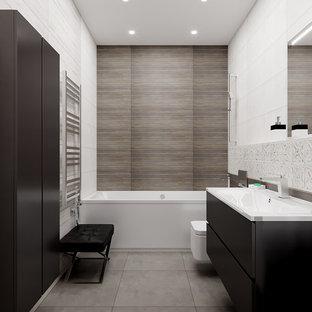 Идея дизайна: туалет среднего размера в стиле лофт с плоскими фасадами, черными фасадами, инсталляцией, серой плиткой, керамической плиткой, серыми стенами, полом из керамогранита, подвесной раковиной, серым полом и белой столешницей