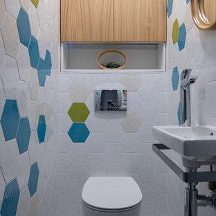 Пример оригинального дизайна интерьера: туалет в современном стиле с инсталляцией, белой плиткой, разноцветной плиткой, подвесной раковиной и белым полом