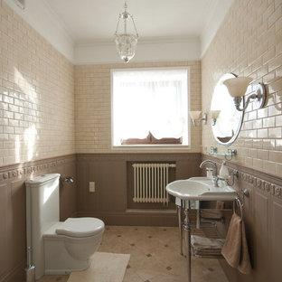На фото: туалет в классическом стиле с унитазом-моноблоком, бежевой плиткой, коричневой плиткой, консольной раковиной и коричневым полом