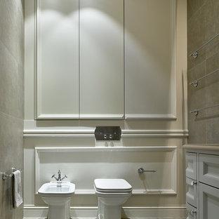 Стильный дизайн: туалет в классическом стиле с биде, белыми стенами, фасадами с утопленной филенкой, белыми фасадами и серым полом - последний тренд