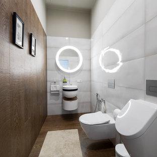 На фото: туалет среднего размера с плоскими фасадами, белыми фасадами, писсуаром, керамогранитной плиткой, полом из керамогранита, подвесной раковиной, коричневым полом, белой плиткой и коричневой плиткой с