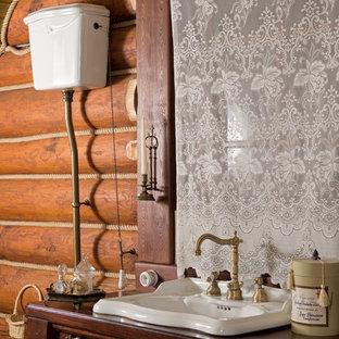 Пример оригинального дизайна интерьера: туалет в стиле рустика с фасадами островного типа, темными деревянными фасадами, накладной раковиной и столешницей из дерева