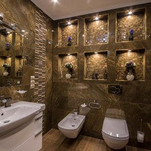 Пример оригинального дизайна интерьера: туалет в современном стиле с плоскими фасадами, белыми фасадами, биде, коричневой плиткой, коричневыми стенами, накладной раковиной и коричневым полом