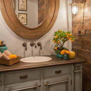 Пример оригинального дизайна интерьера: туалет в классическом стиле с серыми фасадами, белыми стенами, накладной раковиной и коричневой столешницей