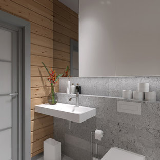 Réalisation d'un petit WC et toilettes nordique avec un placard à porte plane, des portes de placard grises, un WC suspendu, un carrelage gris, des dalles de pierre, un mur gris, un sol en carrelage de porcelaine, un lavabo suspendu, un plan de toilette en granite et un sol gris.