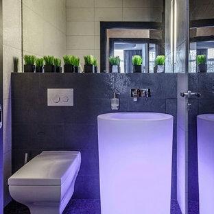 Cette photo montre un petit WC et toilettes chic avec un WC suspendu, des carreaux de porcelaine, un mur gris, un sol en carrelage de porcelaine, un lavabo de ferme et un sol noir.