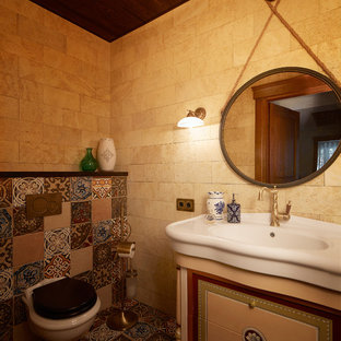 Design ideas for a small mediterranean cloakroom in Yekaterinburg with a wall mounted toilet, beige tiles, multi-coloured tiles, beige walls, mosaic tile flooring, multi-coloured floors, travertine tiles and an integrated sink.