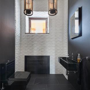 Свежая идея для дизайна: туалет в современном стиле с подвесной раковиной, черными стенами, унитазом-моноблоком и черным полом - отличное фото интерьера