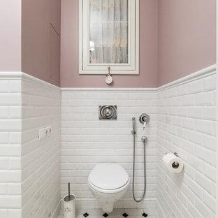 Modelo de aseo clásico con sanitario de pared, baldosas y/o azulejos blancos, baldosas y/o azulejos de cemento, paredes rosas y suelo multicolor