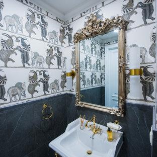 На фото: туалет среднего размера в средиземноморском стиле с черной плиткой, керамогранитной плиткой, белыми стенами, консольной раковиной и обоями на стенах с