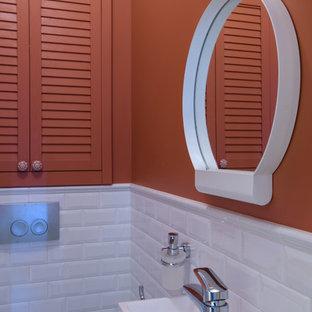 На фото: маленький туалет в скандинавском стиле с инсталляцией, белой плиткой, керамической плиткой, красными стенами, полом из керамической плитки, подвесной раковиной и белым полом с