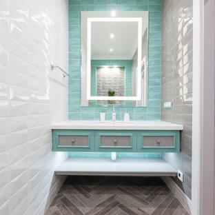 На фото: туалет в стиле современная классика с фасадами с утопленной филенкой, серыми фасадами, синей плиткой, серой плиткой, зеленой плиткой, белой плиткой, керамической плиткой, паркетным полом среднего тона, врезной раковиной, серым полом и белой столешницей с