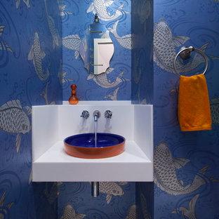 Неиссякаемый источник вдохновения для домашнего уюта: туалет в современном стиле с синими стенами, столешницей из искусственного камня, настольной раковиной и разноцветным полом