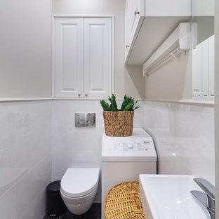 Неиссякаемый источник вдохновения для домашнего уюта: туалет в современном стиле с инсталляцией, белой плиткой, бежевыми стенами, подвесной раковиной и черным полом