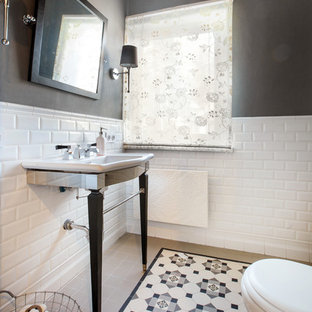 This is an example of a traditional cloakroom in Yekaterinburg with white tiles, multi-coloured tiles, metro tiles, black walls, a console sink and multi-coloured floors.