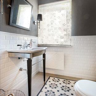 На фото: туалет в стиле современная классика с белой плиткой, разноцветной плиткой, плиткой кабанчик, черными стенами, консольной раковиной и разноцветным полом с