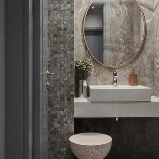 Свежая идея для дизайна: туалет в современном стиле с керамогранитной плиткой, полом из керамогранита, настольной раковиной, серой плиткой и серым полом - отличное фото интерьера