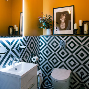 Photo of a contemporary cloakroom in Moscow with flat-panel cabinets, white cabinets, a wall mounted toilet, black and white tiles, orange walls, an integrated sink and multi-coloured floors.