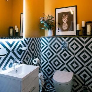 Exemple d'un WC et toilettes tendance avec un placard à porte plane, des portes de placard blanches, un WC suspendu, un carrelage noir et blanc, un mur orange, un lavabo intégré et un sol multicolore.