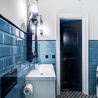 Cette image montre un petit WC et toilettes urbain avec un placard à porte affleurante, des portes de placard blanches, un WC suspendu, un carrelage bleu, des carreaux de céramique, un mur bleu, un sol en carrelage de céramique, une vasque, un plan de toilette en surface solide, un sol noir, un plan de toilette blanc, meuble-lavabo sur pied, un plafond à caissons et du lambris.