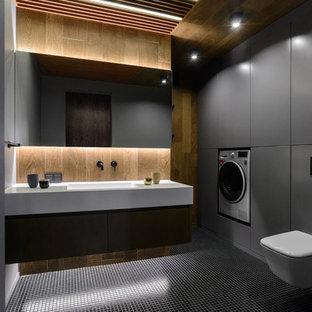 Пример оригинального дизайна: туалет в современном стиле с серыми фасадами, инсталляцией, монолитной раковиной, черным полом и белой столешницей