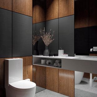 Inspiration pour un WC et toilettes urbain de taille moyenne avec un placard à porte shaker, des portes de placard beiges, un bidet, une plaque de galets, un plan de toilette en surface solide, un carrelage gris, un mur noir, un sol en carrelage de porcelaine, un lavabo suspendu et un sol gris.