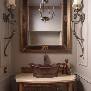 На фото: туалет в классическом стиле с коричневыми фасадами, бежевыми стенами, настольной раковиной и бежевой столешницей с
