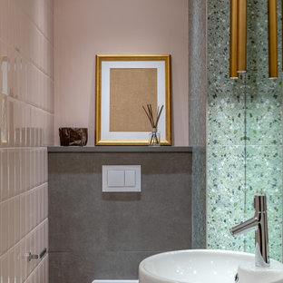Modelo de aseo actual, pequeño, con sanitario de pared, baldosas y/o azulejos rosa, baldosas y/o azulejos grises, baldosas y/o azulejos de cerámica, paredes rosas, suelo de baldosas de porcelana, encimera de acrílico, suelo gris, encimeras grises y lavabo con pedestal