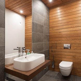 Идея дизайна: маленький туалет в современном стиле с инсталляцией, серой плиткой, плиткой из сланца, разноцветными стенами, полом из сланца, настольной раковиной, столешницей из дерева, серым полом и коричневой столешницей