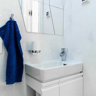 Пример оригинального дизайна интерьера: туалет в современном стиле с плоскими фасадами, белыми фасадами, белой плиткой и монолитной раковиной