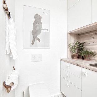 Ispirazione per un piccolo bagno di servizio industriale con ante lisce, ante bianche, pareti bianche, pavimento con piastrelle in ceramica, pavimento bianco, WC sospeso, top in legno, top beige e lavabo da incasso