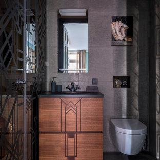 Idee per un piccolo bagno di servizio chic con ante lisce, ante in legno scuro, WC sospeso, piastrelle grigie, piastrelle di pietra calcarea, pareti grigie, pavimento in pietra calcarea, lavabo sottopiano, top in granito, pavimento grigio e top nero