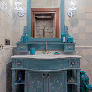 This is an example of a romantic cloakroom in Other with blue cabinets, multi-coloured tiles, ceramic tiles, ceramic flooring, a vessel sink, marble worktops, multi-coloured walls and freestanding cabinets.