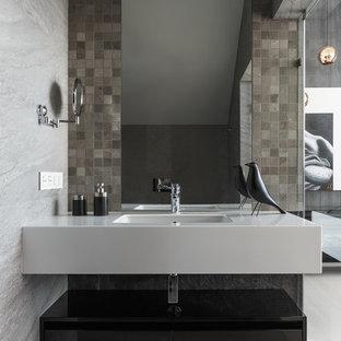 Неиссякаемый источник вдохновения для домашнего уюта: маленький туалет в современном стиле с плоскими фасадами, черными фасадами, серой плиткой, керамогранитной плиткой, полом из керамогранита, врезной раковиной, столешницей из искусственного кварца, серым полом и белой столешницей