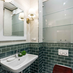 This is an example of a classic cloakroom in Other with glass-front cabinets, a wall mounted toilet, green tiles, white tiles, a wall-mounted sink and white floors.