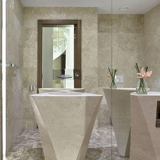 Modelo de aseo actual, grande, con baldosas y/o azulejos beige, baldosas y/o azulejos de travertino, paredes beige, suelo de mármol, lavabo con pedestal y suelo beige