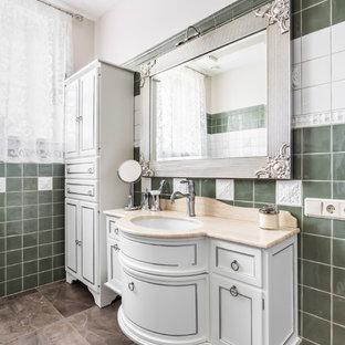 На фото: туалет среднего размера в классическом стиле с фасадами с утопленной филенкой, белыми фасадами, зеленой плиткой, керамогранитной плиткой, белыми стенами, полом из керамогранита, врезной раковиной и мраморной столешницей