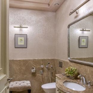 Пример оригинального дизайна интерьера: туалет среднего размера в классическом стиле с плиткой из листового камня, бежевыми стенами, мраморным полом, врезной раковиной, мраморной столешницей, фасадами с выступающей филенкой, бежевыми фасадами, бежевой плиткой и бежевым полом