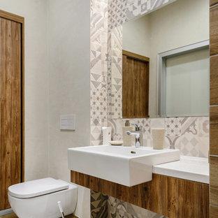 Cette image montre un WC et toilettes design avec un WC suspendu, un carrelage gris, un carrelage blanc, des carreaux de béton, un mur beige, une vasque, un sol beige et un plan de toilette blanc.