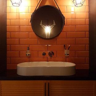 Пример оригинального дизайна: маленький туалет в современном стиле с фасадами с филенкой типа жалюзи, желтыми фасадами, унитазом-моноблоком, желтой плиткой, керамической плиткой, черными стенами, полом из керамогранита, настольной раковиной, столешницей из дерева, серым полом и черной столешницей