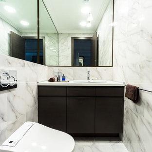 На фото: туалет в современном стиле с плоскими фасадами, черными фасадами, серой плиткой и накладной раковиной с